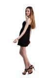 Aantrekkelijke jonge vrouw in een zwarte kleding die en c glimlachen bekijken Stock Foto