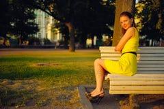 Aantrekkelijke jonge vrouw in gele kleding, die in een de zomerpark zitten op een bank Royalty-vrije Stock Afbeelding