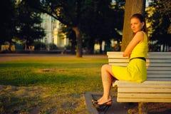 Aantrekkelijke jonge vrouw in gele kleding, die in een de zomerpark zitten op een bank Royalty-vrije Stock Foto