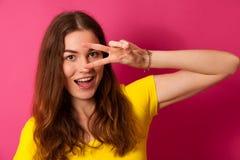 Aantrekkelijke jonge vrouw in gele t-shirt over trillende roze backg Stock Foto's