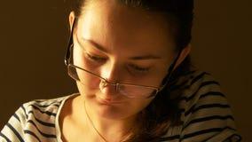 Aantrekkelijke jonge vrouw in glazen die thuis werken stock videobeelden