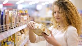Aantrekkelijke jonge vrouw het kopen producten Het kijken en het kiezen stock videobeelden