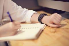 Aantrekkelijke jonge vrouw in het slimme horloge van de bureaunota frome op bureau Stock Afbeeldingen