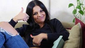 Aantrekkelijke jonge vrouw met duim die omhoog O.K. teken doen stock footage