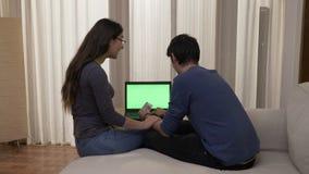 Aantrekkelijke jonge vrouw met glazen die haar vriend proberen te overtuigen om online het winkelen te doen stock video
