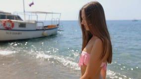 Aantrekkelijke jonge vrouw met lang recht haar in een roze bikini die langs de kust van het strand lopen stock video