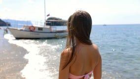 Aantrekkelijke jonge vrouw met lang recht haar in een roze bikini die langs de kust van het strand lopen stock videobeelden
