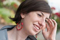 Aantrekkelijke jonge vrouw met rode oorringen Royalty-vrije Stock Foto's