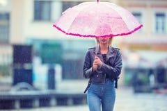 Aantrekkelijke jonge vrouw met roze paraplu in de regen en de sterke wind Meisje met paraplu in de herfstweer Royalty-vrije Stock Afbeelding