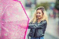 Aantrekkelijke jonge vrouw met roze paraplu in de regen en de sterke wind Meisje met paraplu in de herfstweer Stock Afbeeldingen