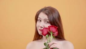 Aantrekkelijke jonge vrouw met rozen in haar hand het stellen voor camera stock videobeelden