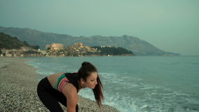 Aantrekkelijke jonge vrouw op een strand die een steen werpen in het water stock footage