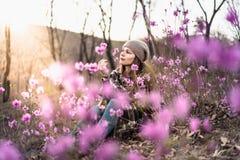 Aantrekkelijke jonge vrouw in openlucht met tot bloei komende roze bloemen stock afbeeldingen
