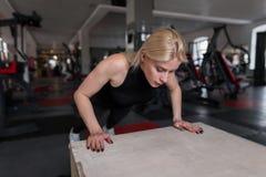 Aantrekkelijke jonge vrouw in sportkleding die opdrukoefeningen in een geschiktheidsstudio doet Het meisje doet de lading op de h royalty-vrije stock foto