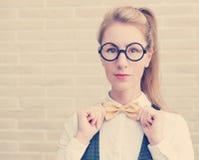 Aantrekkelijke jonge vrouw in vest en vlinderdas die glazen dragen Stock Afbeelding