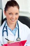Aantrekkelijke jonge vrouwelijke arts die een klembord houdt Stock Afbeelding