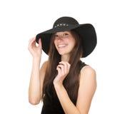 Aantrekkelijke jonge vrouwelijke mannequin die met zwarte hoed glimlachen royalty-vrije stock foto's