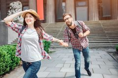 Aantrekkelijke jonge vrouwelijke voorwaartse toeristengang Zij glimlacht De hand en de hoed van de jonge vriend van de vrouwengre stock fotografie