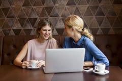 Aantrekkelijke jonge vrouwen met laptop in de koffie Stock Foto