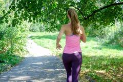 Aantrekkelijke jonge vrouwenjogging op parksleep Gezond levensstijlconcept royalty-vrije stock fotografie