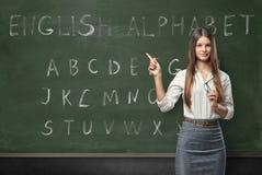 Aantrekkelijke jonge vrouwenleraar in een klaslokaal royalty-vrije stock foto