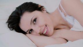 Aantrekkelijke jonge vrouwenontwaken in bed thuis Het meisje kijkt aan camera en leuke glimlachen Verse en gelukkige vrouw in och royalty-vrije stock afbeelding