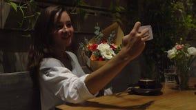 Aantrekkelijke jonge vrouwenzitting in koffie met koffiekop, met bloemen die camera bekijken stock videobeelden