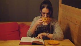 Aantrekkelijke jonge vrouwenzitting in koffie op een bank die een boek lezen en een koffie drinken stock footage