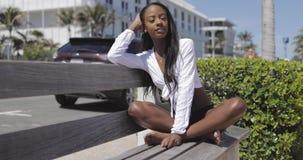 Aantrekkelijke jonge vrouwenzitting op bank op zee stock videobeelden