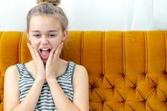 Aantrekkelijke jonge vrouwenzitting op de bank thuis met verrassingsuitdrukking op het gezicht stock afbeelding