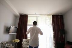 Aantrekkelijke jonge zakenman in wit klassiek overhemd terwijl status dichtbij het venster royalty-vrije stock afbeeldingen