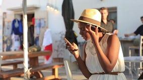 Aantrekkelijke jonge zwarte modieuze vrouw in hoedenzitting door een straat en het spreken op celtelefoon met helder zonlicht stock video