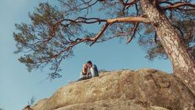 Aantrekkelijke jongeren die op de rand van een rotsachtige verlaten heuvel omhelzen Groen dicht bos rond Romantische atmosfeer stock footage