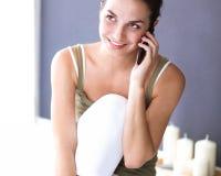 Aantrekkelijke Kaukasische meisjeszitting op vloer die op de telefoon spreken Stock Fotografie