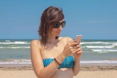 Aantrekkelijke Kaukasische mooie vrouw in bikini het texting op de achtergrond van het overzees op strand Royalty-vrije Stock Afbeeldingen
