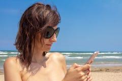 Aantrekkelijke Kaukasische mooie vrouw in bikini het texting op de achtergrond van het overzees op strand Stock Foto's
