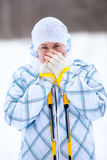 Wijfje die bevroren handen met skistokken verwarmen Royalty-vrije Stock Fotografie