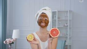 Aantrekkelijke Kaukasische vrouw die en pret met de helft van citroen en grapefruit met bruin masker op het gezicht stellen hebbe stock video