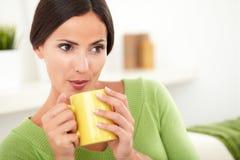 Aantrekkelijke Kaukasische vrouw die op hete koffie blazen stock foto's
