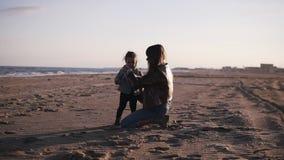 Aantrekkelijke Kaukasische vrouw met baby op de avond overzeese promenade Jonge moeder die de dochter in haar wapens houden stock videobeelden