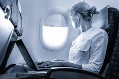 Aantrekkelijke Kaukasische vrouwelijke passagier die door het duidelijke venster kijken terwijl het werken bij het moderne laptop stock afbeeldingen