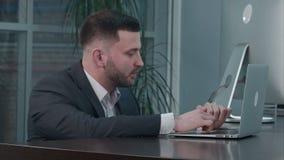 Aantrekkelijke Kaukasische zakenman die laptop met behulp van, terwijl het spreken met partner op het werk stock videobeelden