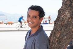 Aantrekkelijke kerel bij Rio de Janeiro-het ontspannen op een boom Royalty-vrije Stock Afbeeldingen