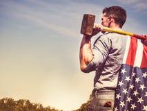 Aantrekkelijke kerel, voorhamer en een vlag van de V.S. Stock Afbeelding