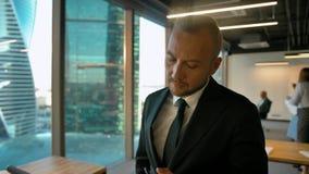 Aantrekkelijke knappe werkgever in bureau die openspace en met zijn overeenkomstenpartner typen babbelen stock videobeelden