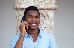 Aantrekkelijke Latijnse kerel met telefoon in een koloniale stad Stock Foto's