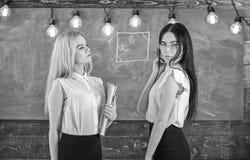 Aantrekkelijke leraren die zich na klassen overwerken Dames klaar om privé-les, bord op achtergrond te beginnen privé royalty-vrije stock fotografie