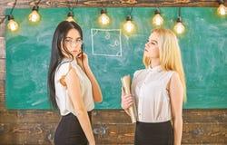 Aantrekkelijke leraren die zich na klassen overwerken Dames klaar om privé-les, bord op achtergrond te beginnen privé stock afbeelding