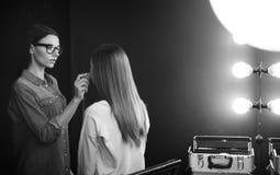 Aantrekkelijke leuke make-upkunstenaar die een sponsinstrument met behulp van Stock Fotografie