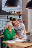Aantrekkelijke maatschappelijk werker bijwonende oma in het berekenen met documenten royalty-vrije stock afbeeldingen